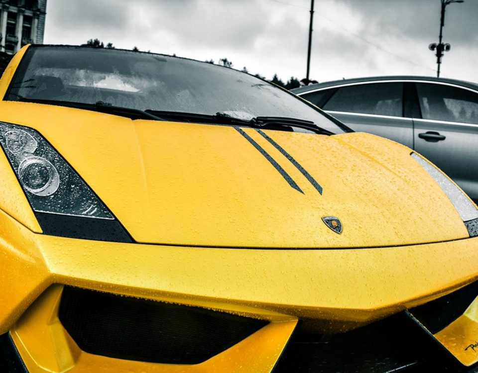 The Yellow Lamborghini Car With Another Black Car Under The Rainy Clouds