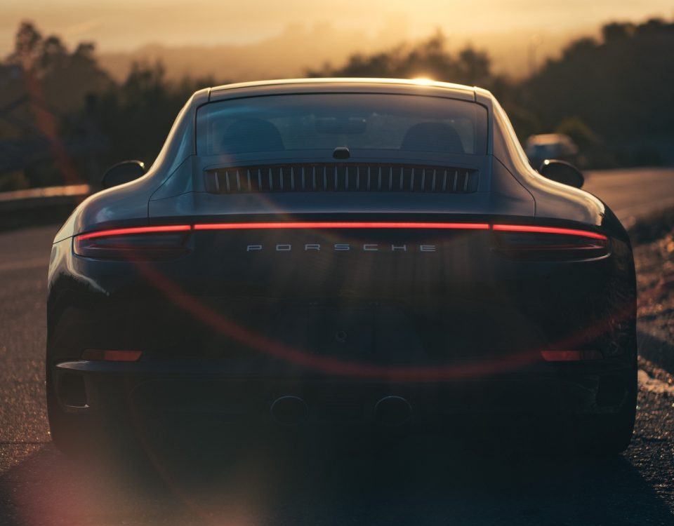 Black Porsche 918 Rear View In Sunset On Road