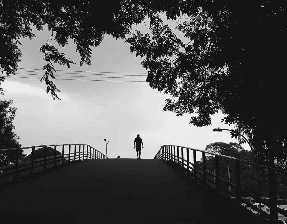 A Man Is Walking Alone On A Black Bridge