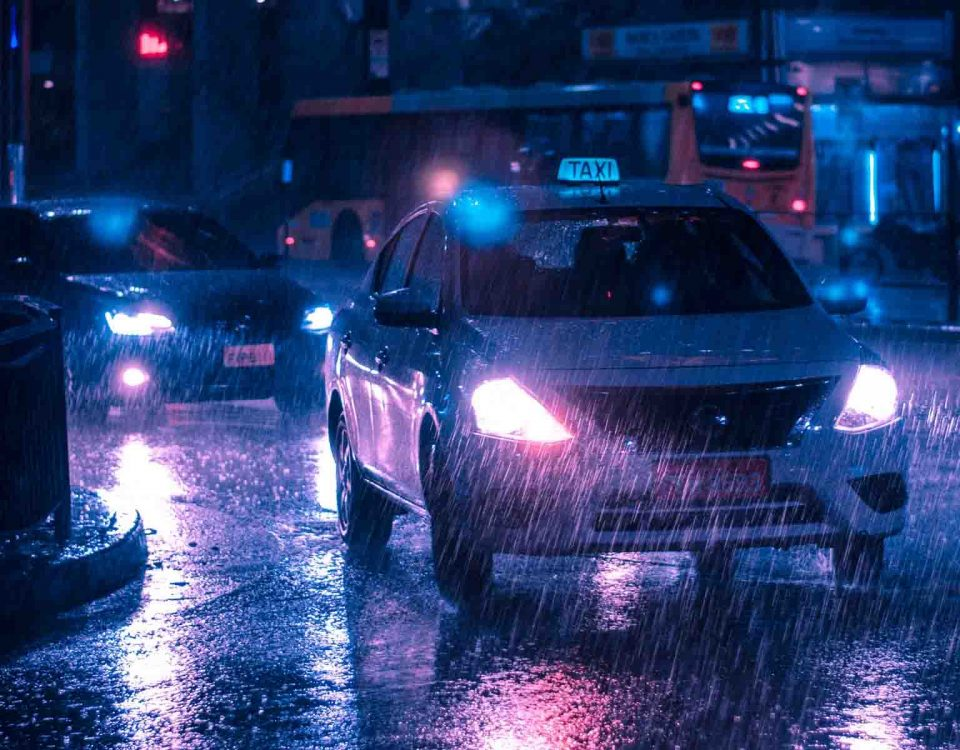 White Taxi With On Headlights In Rain