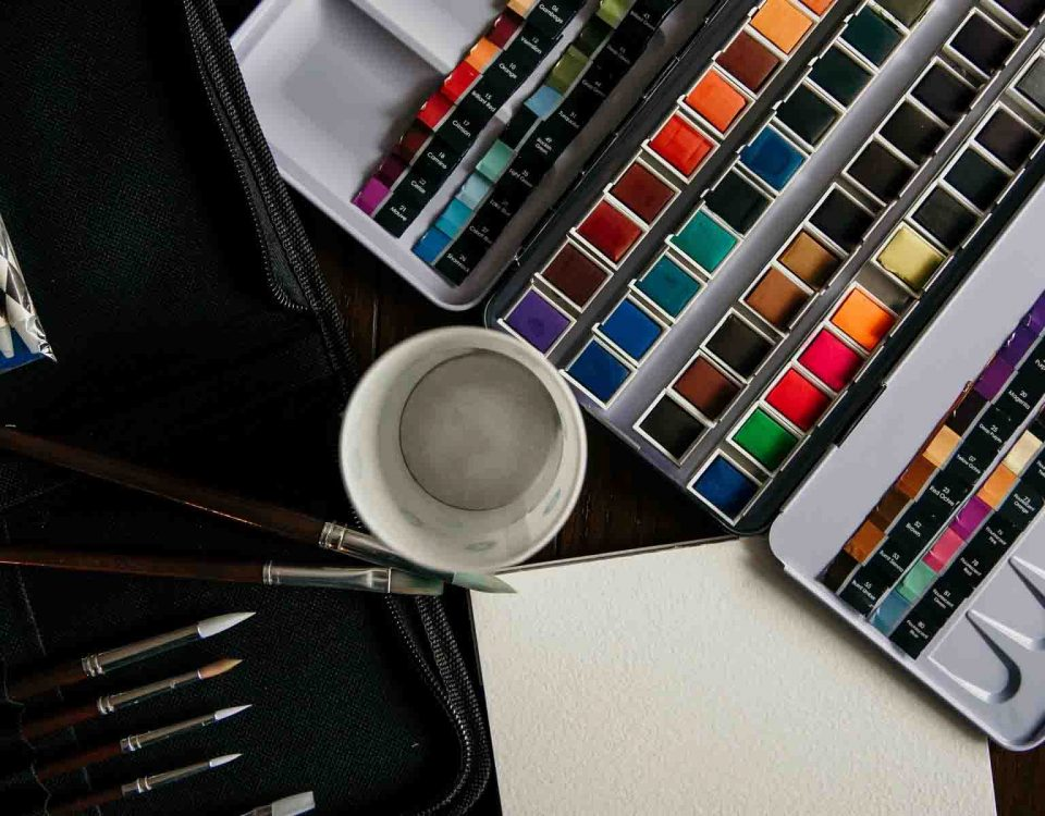 Artistic Tools, Watercolors, Paper And An Empty Cup On A Table