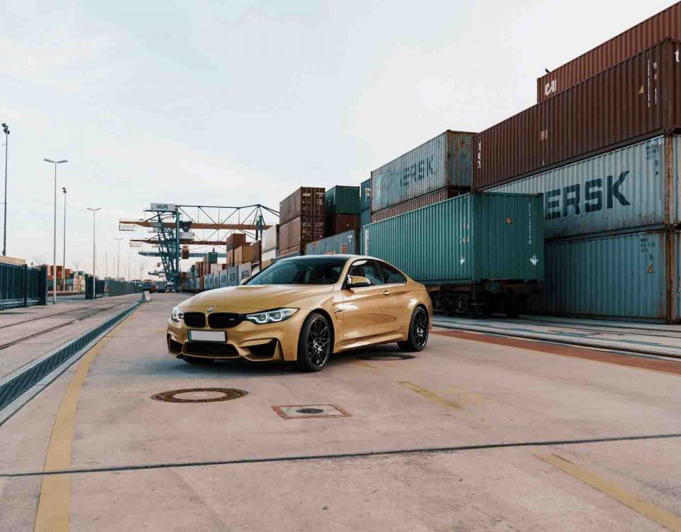Beige Color BMW Car Standing Near Containers