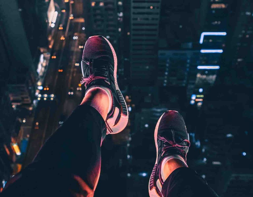 A Girl Is Sitting On A Building Roof Edge And Her Feet's Are Above The City