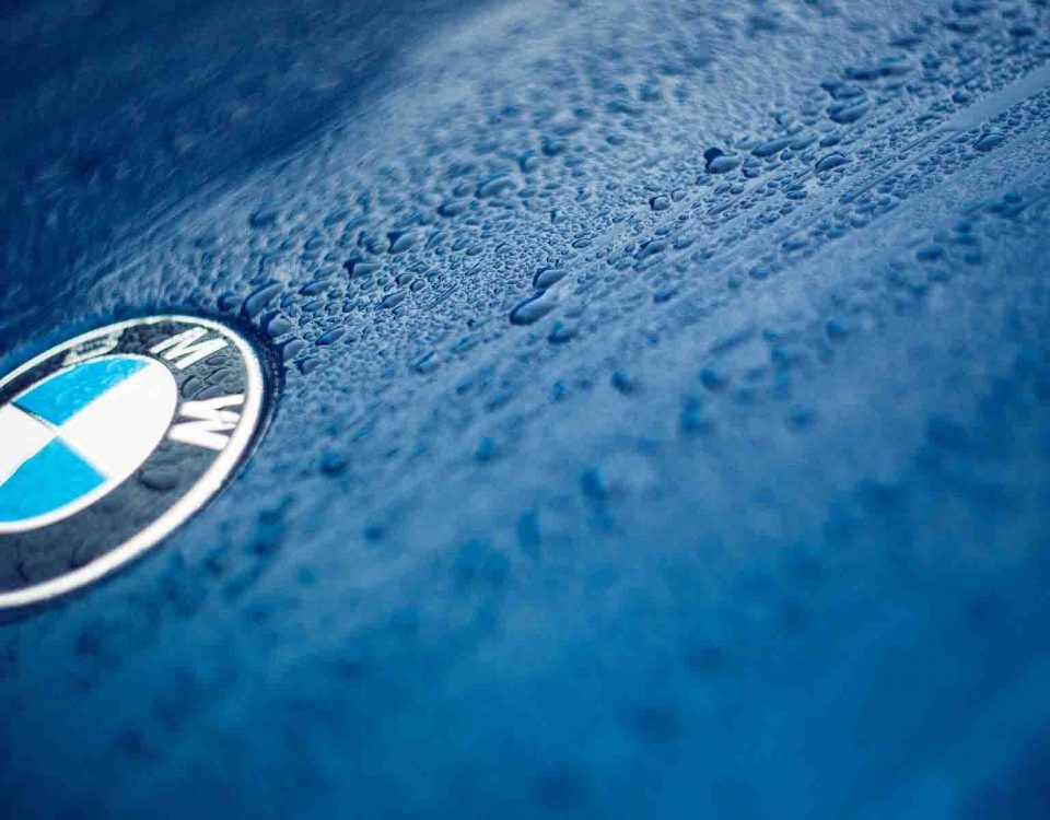 BMW Logo On Wet Blue Car