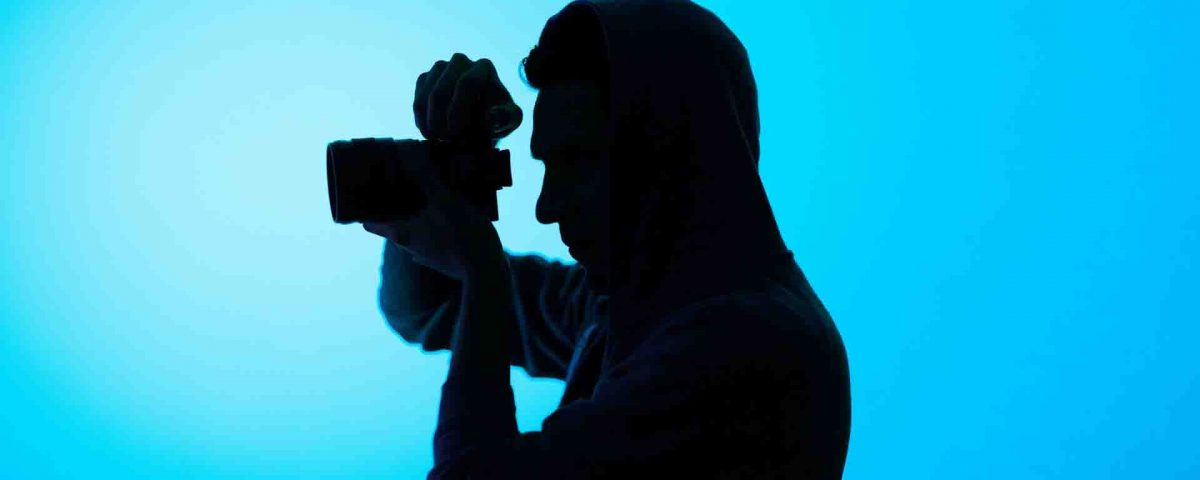 A Man Is Shooting With Camera On Blue Background